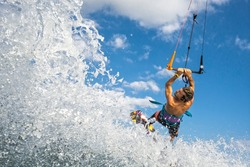 professional kiter makes the difficult trick on a beautiful background of spray and beautiful mountains of Mauritius