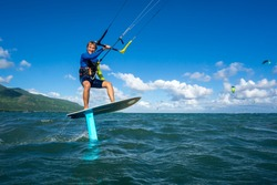 professional kiter t rides by hydrofoil on a beautiful background of mountain, spray and beautiful clouds of Mauritius
