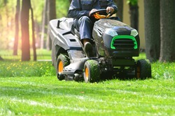 Professional lawn mower with worker cutting the grass in a garden