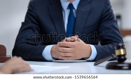 Professional lawyer carefully listening to client and giving advices, close-up