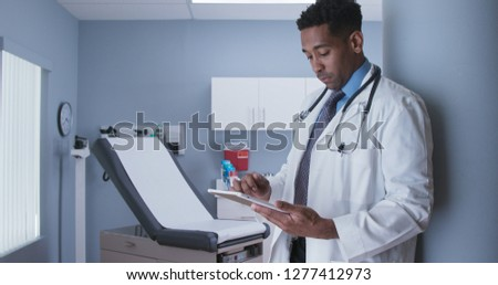 Professional licensed MD using tablet computer inside health clinic