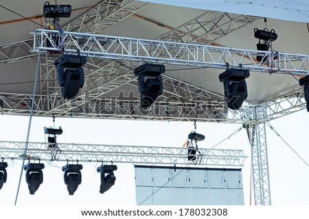 Professional lighting equipment high above an outdoor theatrical performance