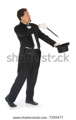 Professional magician wearing tuxedo performing on a white background