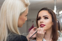 Professional make-up artist applying bright red lipstick on beautiful girl using special lip brush.