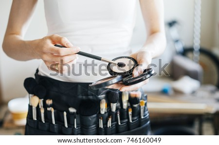 professional make-up artist with a belt bag with tassels. makeup brushes.