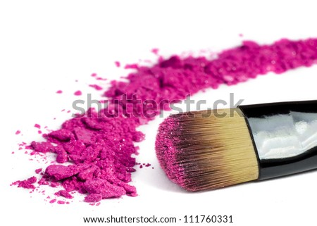 Professional make-up brush on pink crushed eyeshadow