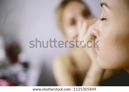 professional make-up in the beauty salon / master makes a professional fresh summer make-up of a beautiful model in the salon #1125305849