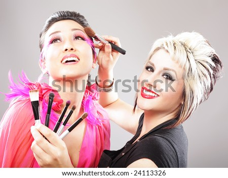stock photo : Professional makeup artist applying cosmetics to a model's