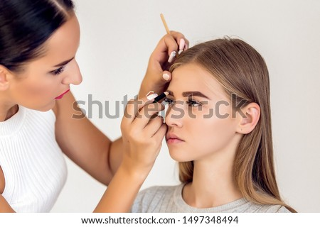 Professional makeup artist to do make up beautiful young model. New look in beauty studio. Cosmetics, brushes and visage. Eybrows, crayon, eyebrow pencil