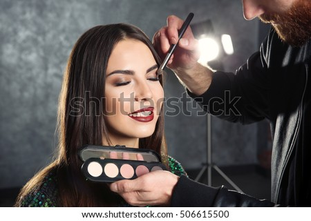 Professional makeup artist working with beautiful young woman #506615500