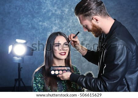Professional makeup artist working with beautiful young woman #506615629