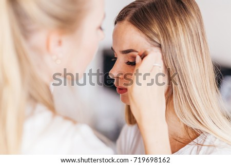"Professional makeup artist working with beautiful young woman in white T-shirt with word ""less"" #719698162"