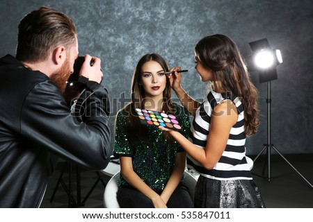 Professional makeup artist working with young beautiful woman at photo shooting #535847011