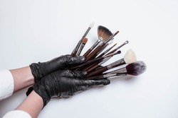 Professional makeup brushes isolated on white background. Hand in a black glove holds a set of professional brushes for cosmetics on a white background. Copy space for text. Makeup. Brushes.