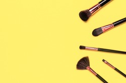 Professional makeup brushes on Illuminating yellow background flat lay top view. Pantone color of year 2021. Beauty product, makeup, women's accessory, fashion. Different brushes. Cosmetic makeup Set