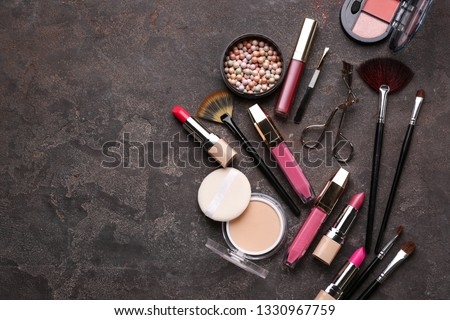 Professional makeup cosmetics with accessories on grey background