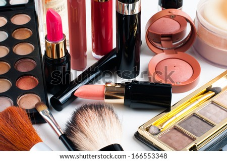 Professional makeup set: eyeshadow palette, lipstick, mascara, blush, powder, make-up brushes and perfume, many cosmetics closeup.