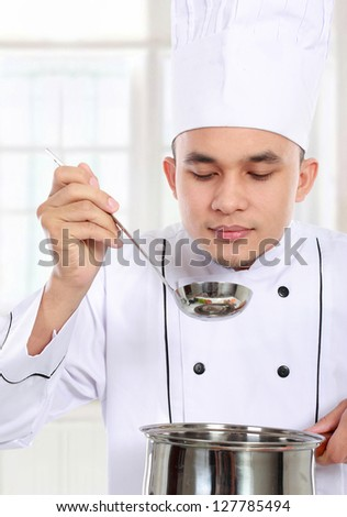 professional male chef smell his cooking in the kitchen