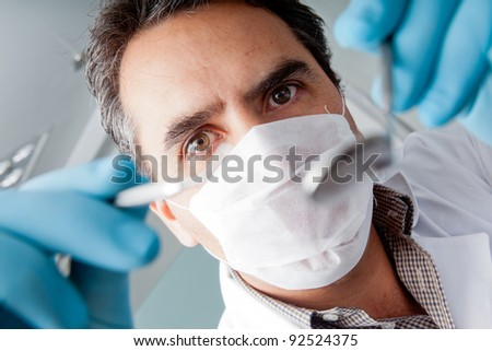 Professional male dentist holding instruments and wearing facemask