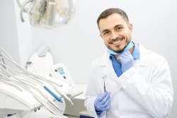 Professional male dentist smiling to the camera holding dental instruments sitting at his office copyspace dentistry profession doctor treatment curing help helpful skilled job worker health medical