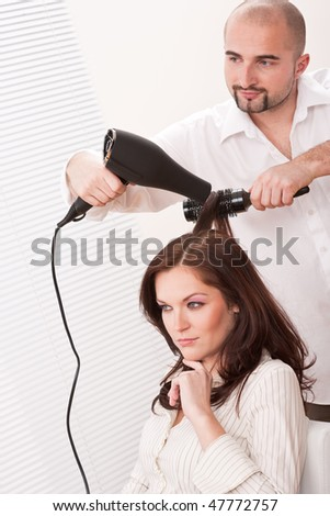 Professional male hairdresser with hair dryer at salon with female customer