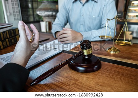 Professional male lawyer or counselor discussing negotiation legal case with client meeting with document contract in office, law and justice, attorney, lawsuit concept.