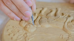 Professional male potter making clay stamp picture. Handwork, crafting and traditional arts concept