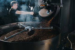 Professional male roaster loading container of steaming machine with coffee beans