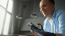 Professional man cyborg with artificial high tech hand in home kitchen