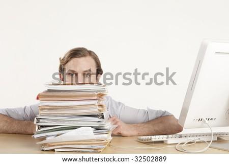 professional man sitting at desk behind stack of paperwork