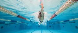 Professional man swimmer inside swimming pool. Underwater panoramic image.