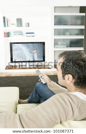 Professional man using a tv remote control to change channels on the television at home.