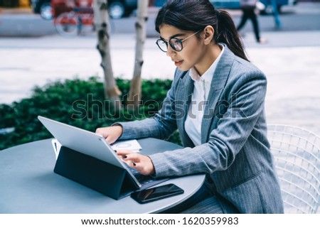 Professional management expert research information on digital tablet while sitting at street cafeteria and messaging with business partners, intelligent woman connected to public 4g internet