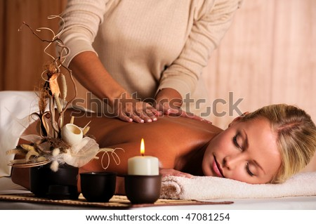 stock photo : professional masseur doing massaging back of a beautiful young