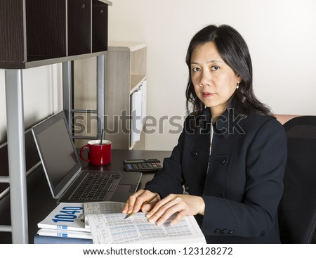 Professional Mature Asian woman working on Personal Income Taxes with tax table booklet, computer, coffee cup with spoon on desk - stock photo