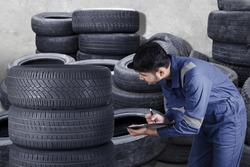 Professional mechanic checking heap of car tyre on clipboard while looking texture of tyre