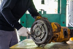 Professional mechanic man inspection hydraulic gear pump of wheel loader in workshop, repair maintenance heavy machinery