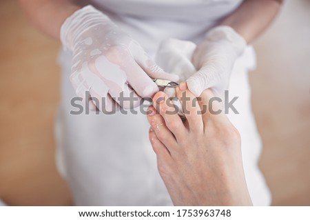 Professional medical pedicure procedure close up using nail clippers instrument. Patient visiting chiropodist podiatrist. Foot treatment in SPA salon. Podiatry clinic. Pedicurist hands in white gloves Stockfoto ©