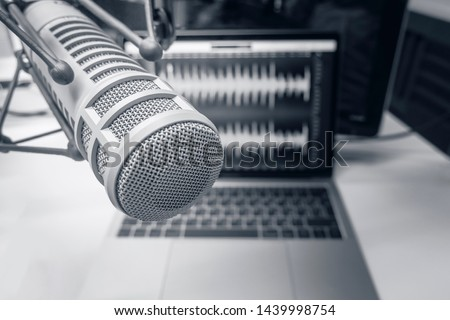 Professional microphone and sound wave form on laptop screen