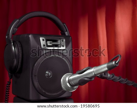 Professional microphone, headphone and speaker with a red curtain on the background.