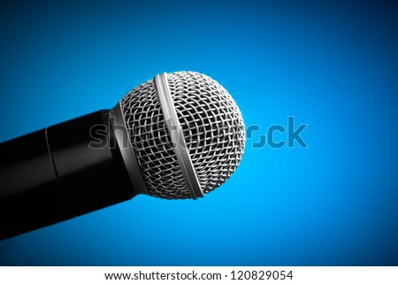 Professional microphone on blue background