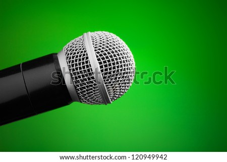 Professional microphone on green background