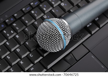 Professional microphone on laptop keyboard - stock photo