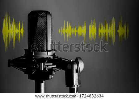Professional microphone with yellow voice waveform on dark background, sound studio recording