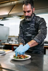 Professional military base chef or cook preparing delicious tasty meal with fresh salmon fish and salad.