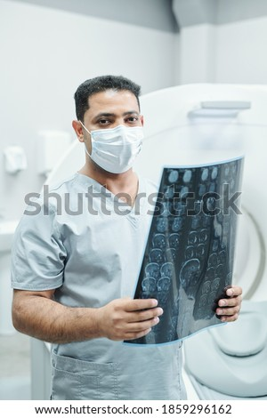 Professional mixed-race radiologist in mask and uniform holding x-ray image of patient head against environment of medical office Stock photo ©