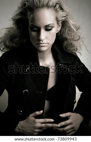 Professional model posing on white background in black coat with styled hair by hairdresser. Half length shot.