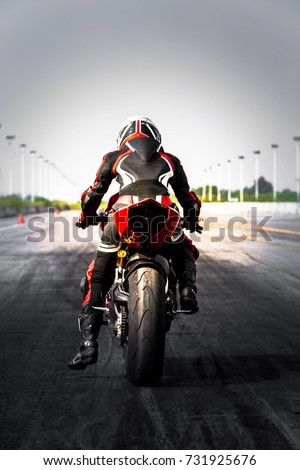 Professional motorcycle rider in leather suit and safety helmet ready to race on race track.