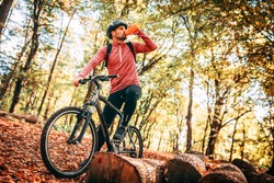Professional mountain bike cyclist riding trail in forest, details of sports. Drinking cold fresh water.