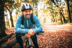 Professional mountain bike cyclist riding trail in forest, details of sports. Toothy smile.